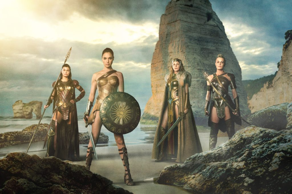 GAL GADOT as Diana standing on beach with other Amazonian women next to her.
