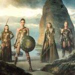 GAL GADOT as Diana standing on beach with other Amazonian women