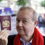 Ian Hislop looking at camera holding up British passport