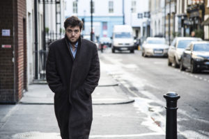 Cormoran Strike (TOM BURKE) walking down street with hands in pockets