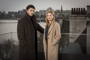 Cormoran Strike (TOM BURKE), Robin Ellacott (HOLLIDAY GRAINGER) standing on bridge looking at camera