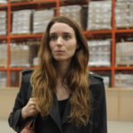 Una (Rooney Mara) standing in warehouse looking forward