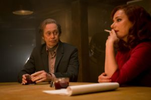 Jill (Sidse Babett Knudsen) and Ed (Steve Buscemi) sitting at a table., Jill is smiking