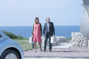 Ed (Steve Buscemi) and Sally (Julia Davis) walking up drive with suitcases in hands and sea behind them