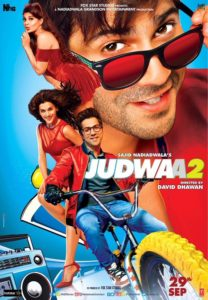 Film poster with actor and actress on bicycle with large close of actors face in background tilting sunglasses forward. Judwaa 2 is written in the middle.