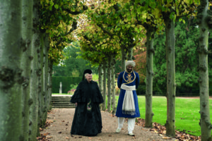 Queen Victoria and Abdul walking on tree lined pathway