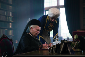 Queen Victoria sitting at table writing with Abdul standing next to hear looking down