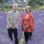 Frank Skinner and Joan Bakewell standing in lavender field looking up