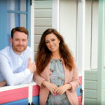presenters standing outside beach hut looking towards camera