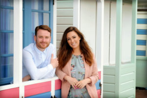 two presenters standing outside beach hut looking towards camera