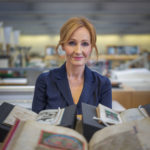 J.K. Rowling looking at forward sitting in front of books