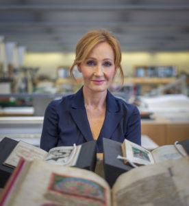 J.K. Rowling sitting at a table, looking at the camera, with a pile of books in front of her,