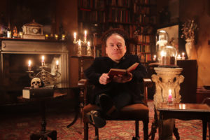 Warwick Davis sitting on chair reading book