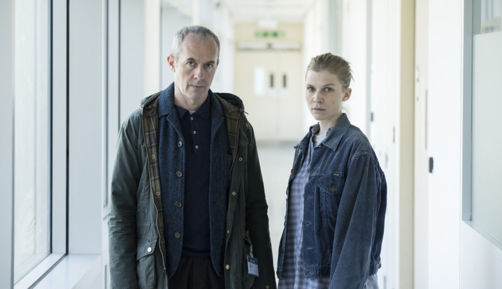 Actors Clémence Poésy and Stephen Dillane look on at camera in police building