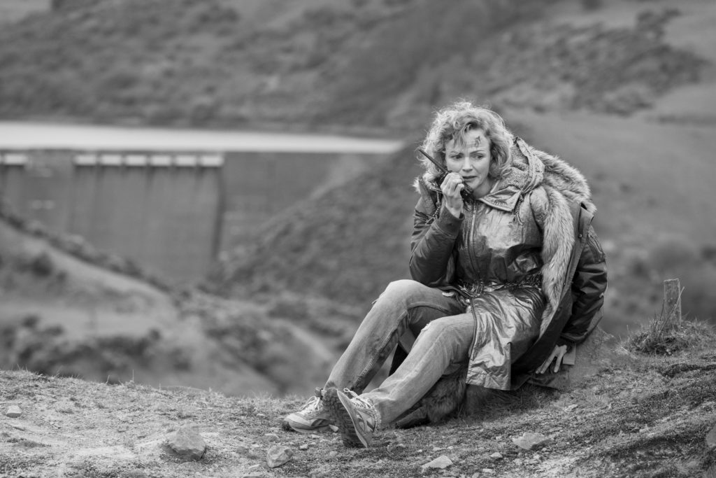 Image of Maxine Peake sat in a remote rural location on the phone with a look of panic on her face