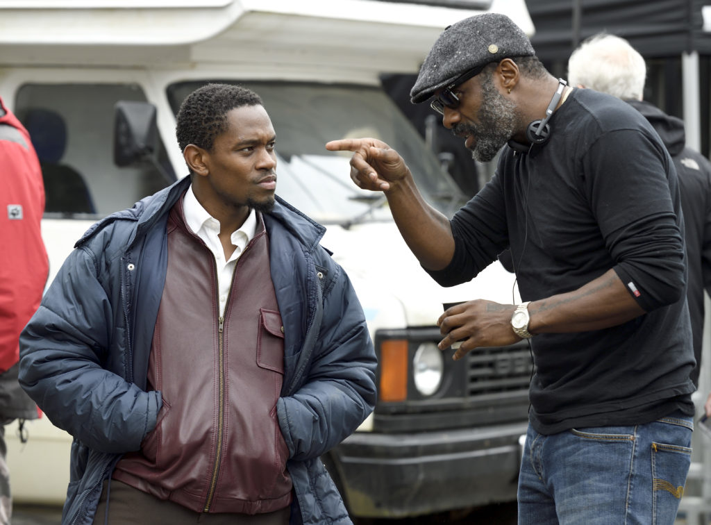 Amel Ameen talking to director Idris Elba on set stood in front of a white van