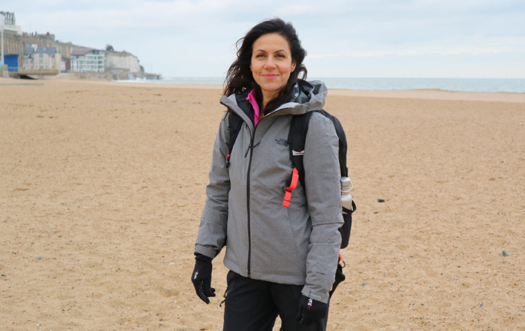 Presenter Julia Bradbury on the beach at Ramsgate starting the Ramsgate to to Margate Walk. Julia wears an outdoor coat and backpack