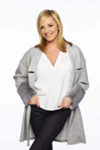 Actress Melanie Owen (TAMZIN OUTHWAITE) smiling with her hands in her pockets. She is wearing a white blouse and grey cardigan. She is on a plain white background.