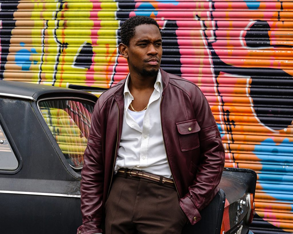 Idris Elba in Yardie leans against a car with a graffiti wall behind. He wears a leather jacket.