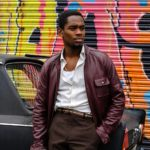 Amel Ameen in Yardie leans against a car with a graffiti wall behind. He wears a leather jacket.