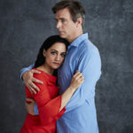 Actress Archie Panjabi and actor Jack Davenport embrace against a grey background