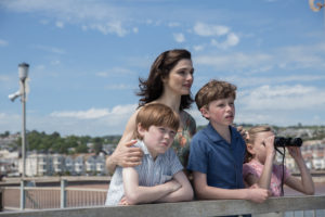 Rachel Weisz in The Mercy 2018. Rachel and 3 children stand against a harbour wall looking out to see.