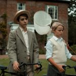 Two young boys stand in an english garden with a manor house behind. They are stood with bicycles and a butterfly net