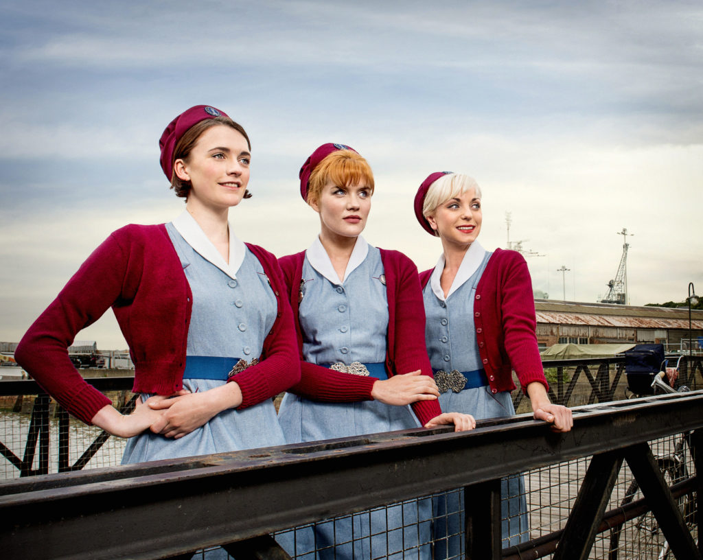 Three characters from call the midwife looking out to sea on a bridge at the Historic Dockyard Chatham with their blue and red midwife uniforms on.