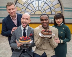 Image of The Great British Bake Off hosts Tom Allen and Liam Charles sitting on stools holding cakes with pastry chef judges Cherish Finden and Benoit Blin standing behind them.