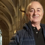 Image of presenter Tony Robinson standing in a cathedral