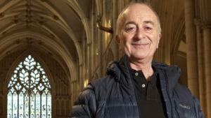 Headshot of presenter Tony Robinson standing in a cathedral with his blue coat on.