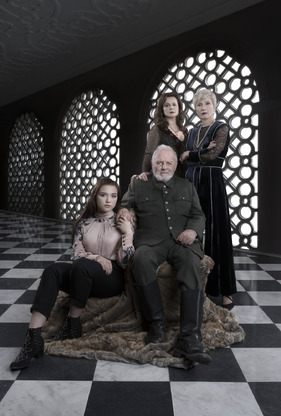 Portrait shot of character King Lear sitting on a chair with his three daughters by his side in the palace. Background is black and white chequered floor with black wall panels.