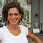 Image of presenter Alex Polizzi wearing a white top in a hotel smiling at the camera