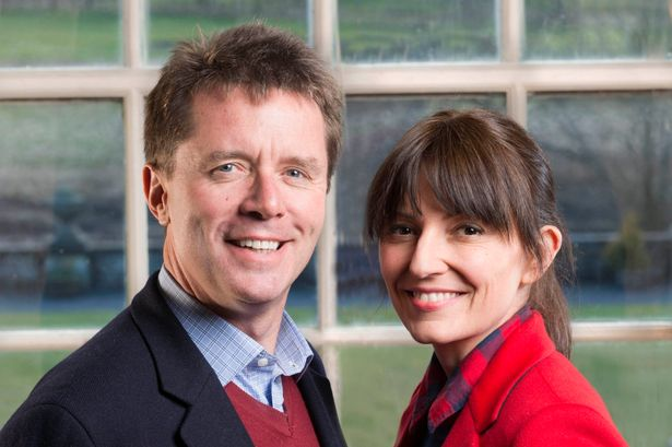 Close up of presenters Davina McCall and Nicky Campbell smiling at the camera. Nicky wearing a blue suit and red jumper, Davina wearing a red jacket and shirt.