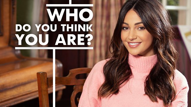 Actress Michelle Keegan smiling at the camera in a pink jumper. Who do you think your are? written in white