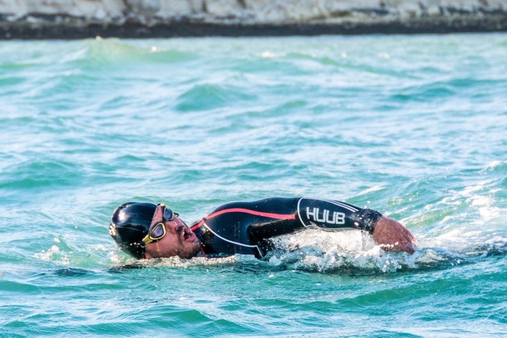 Image of Ross Edgley swimming in the sea in a black wetsuit and goggles.