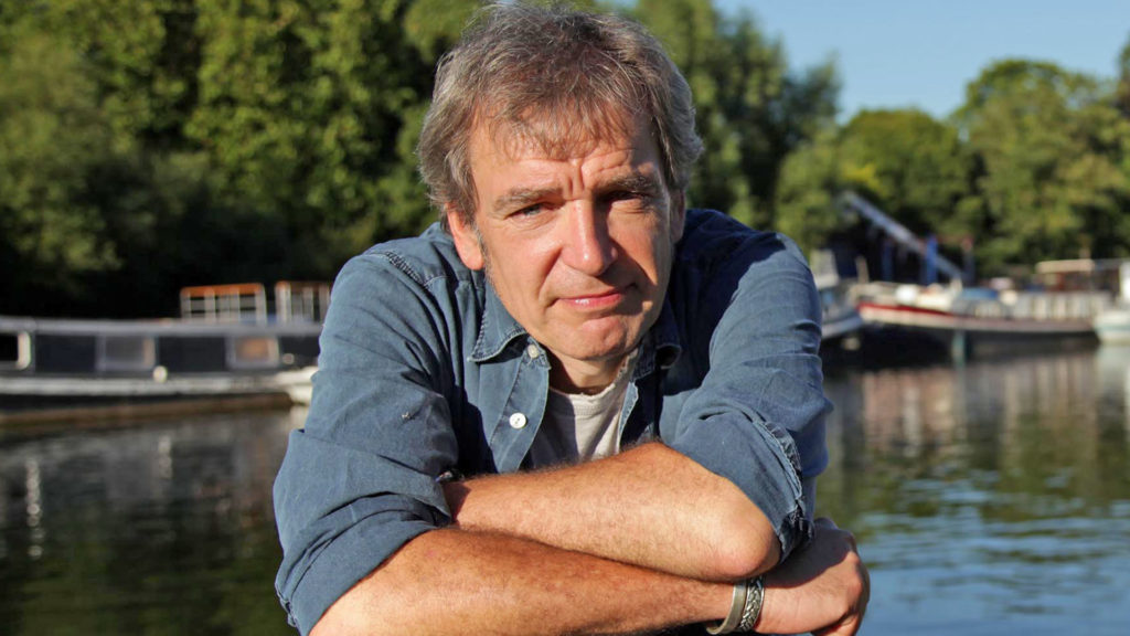 Image of presenter Mark Evans in a blue shirt with his arms crossed, water and canal boats behind him.