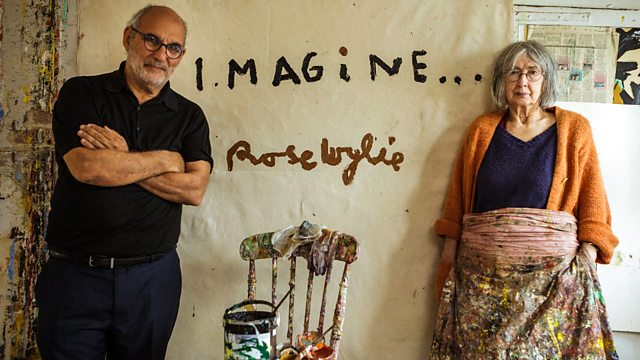 Artist Rose Wylie and presenter Alan Yentob pictured standing together in Rose's home against a messy painted wall.