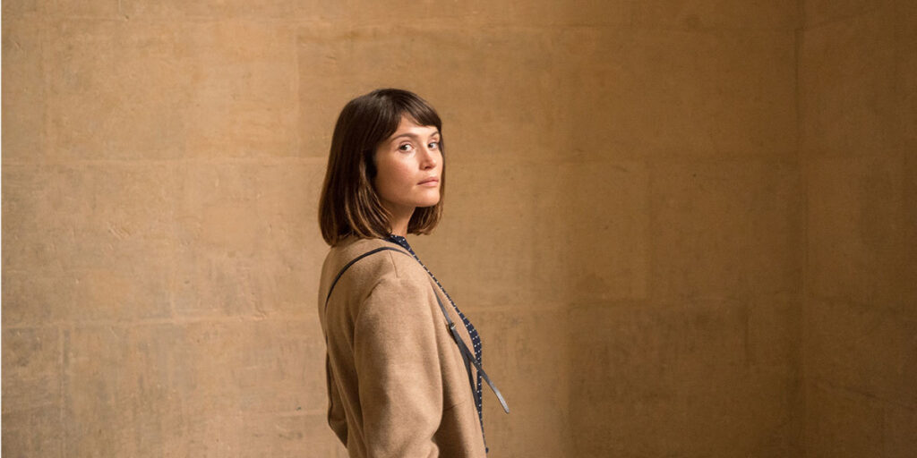 Gemma Arterton staring at the camera with a plain brown background behind her,