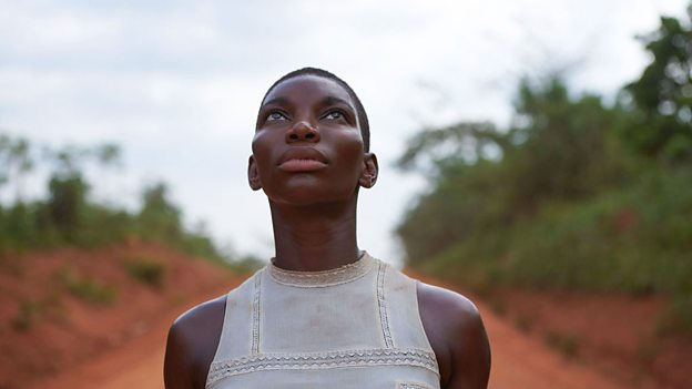 Black Earth Rising Series Poster Image- main character in a dress staring up at the sky on a dirt track with foliage either side.
