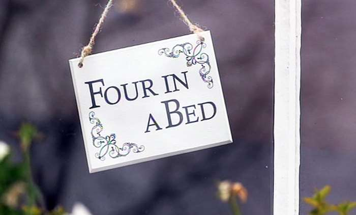 Four in a bed series logo on a white sign hanging in a window