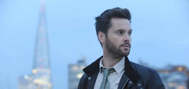 Actor Tom Riley from Dark Heart Series staring away from the camera in a suit and coat. City skyline in background.