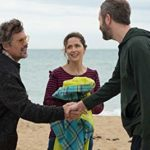 Three actors including Rose Byrne greeting one another on the beach