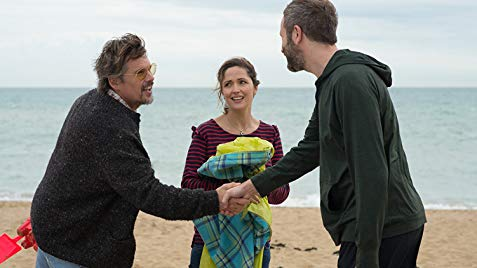 Two actors greeting one another on the beach, actress Rose Byrne is smiling at them in the middle carrying a blanket.