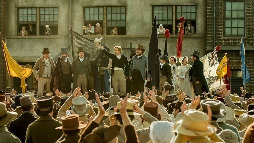 Various actors in film 'Peterloo' standing on a stage, surrounded by a cheering crowd