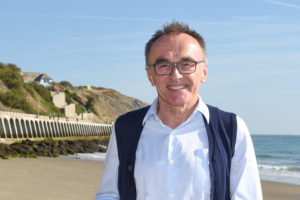 Image of Danny Boyle smiling at the camera in a white shirt on Sunny Sands beach in Folkestone, sea and path can be seen in background