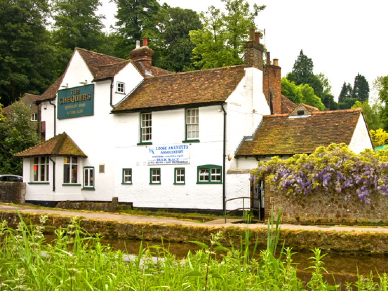 Chequers Inn pub is a white large building situated along the river