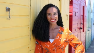 Image of presenter Michelle Ackerley in an orange top leaning against colourful sheds