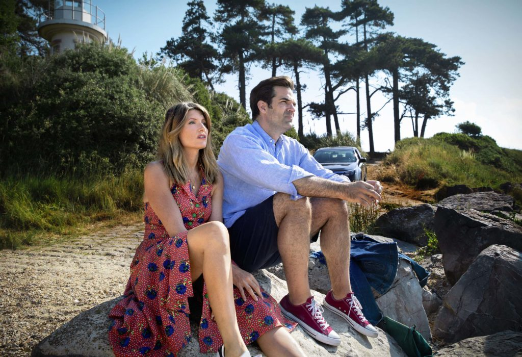 Sharon (Sharon Horgan) and Rob (Rob Delaney) cast from the series. The two are sitting on a rock by the side of the road, looking up to the sky.