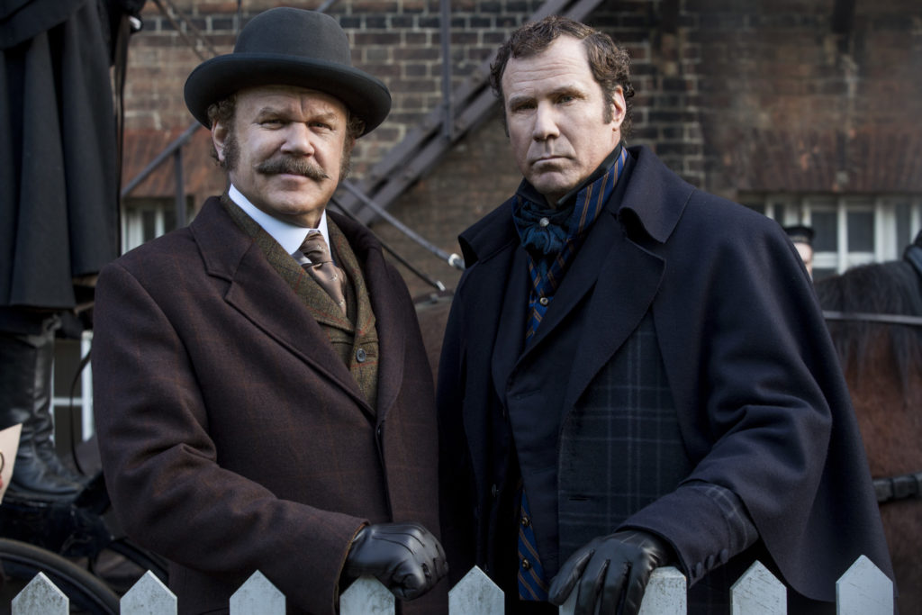 Movie poster of Holmes and Watson (Will Ferrell and John C. Reilly). Both staring into the camera in front of a horse wearing period suits. John is wearing a hat.